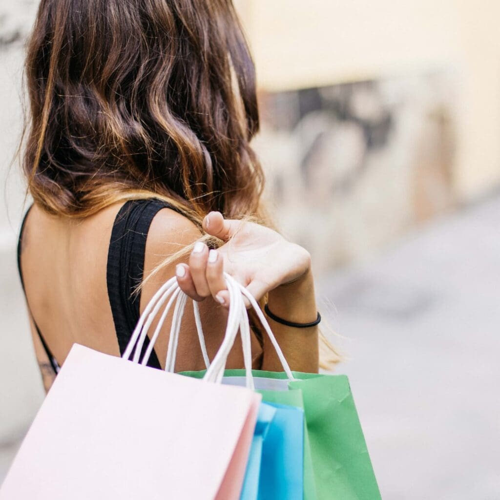 woman walking away with shopping bags full over her shoulder