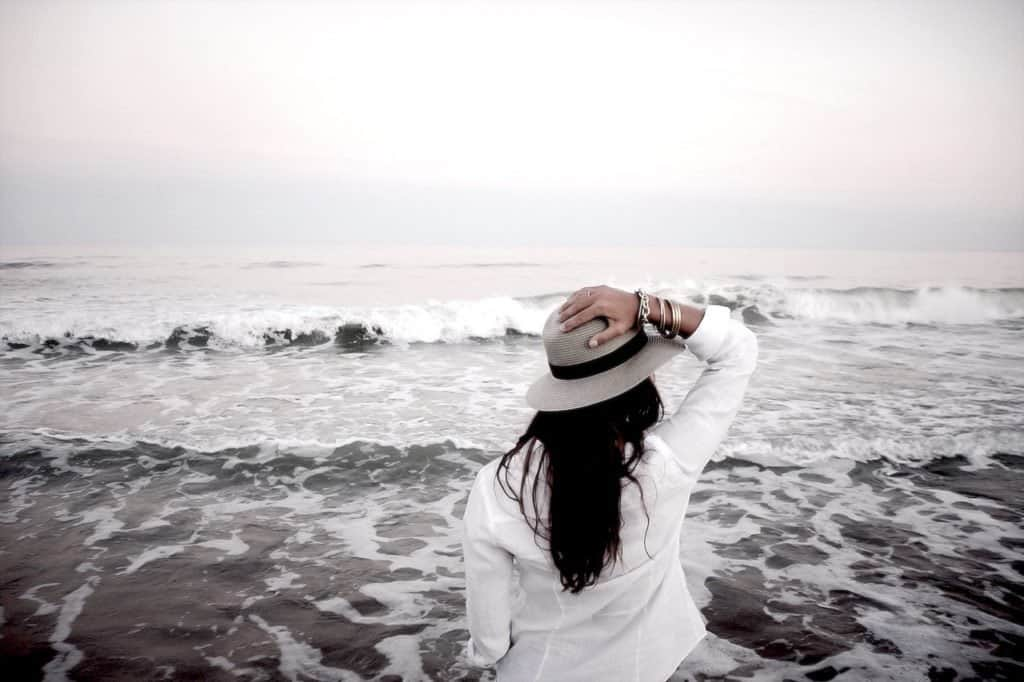Woman in a white shirt wearing a hat and looking out at the ocean like. Looks like she is contemplating life.
