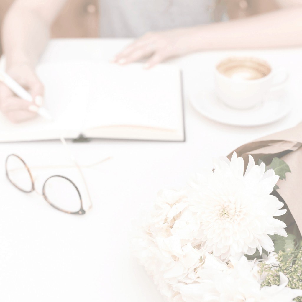 Image of a woman simplifying her life: writing in a journal with a coffee cup, reading glasses and a bouquet of white flowers in the foreground.