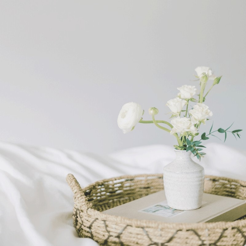 White vase with white flowers in a tray, on white bedding. An image of simple living.