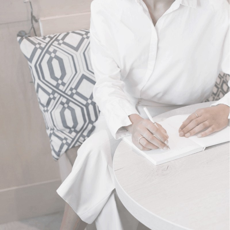 Woman in a white shirt writing in a journal
