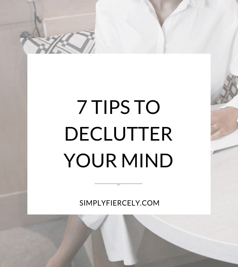 "Text reading ""7 Tips to Declutter Your Mind"" in a white box with a background image of a woman in a white shirt sitting at a desk writing in a journal."