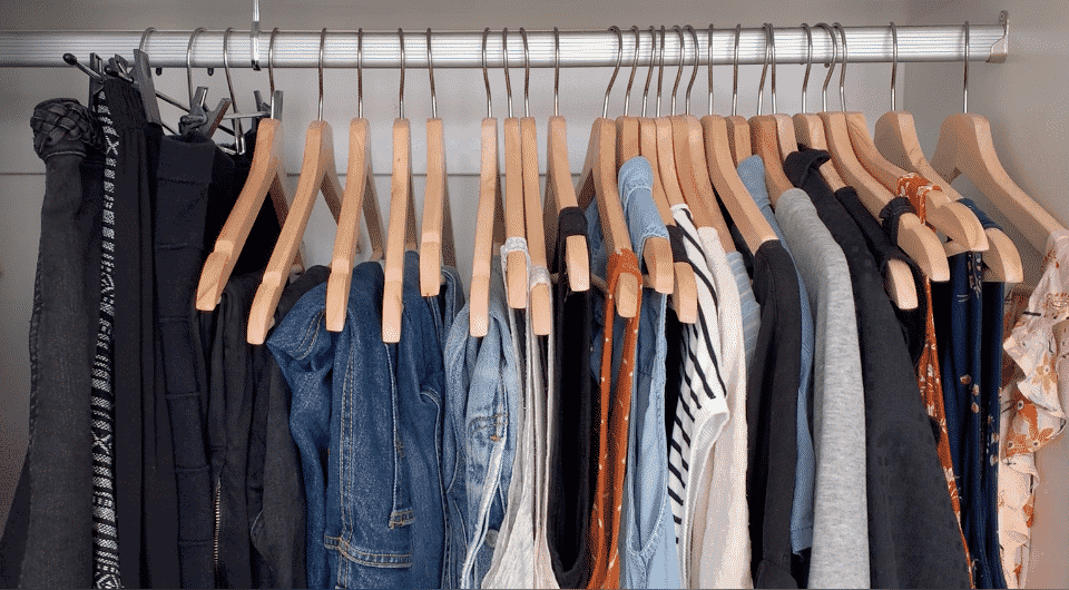 a tidy, minimalist wardrobe hanging in a closet
