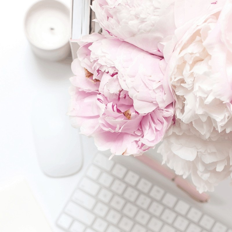 Pink flowers and a white styled flat lay desk in the background.
