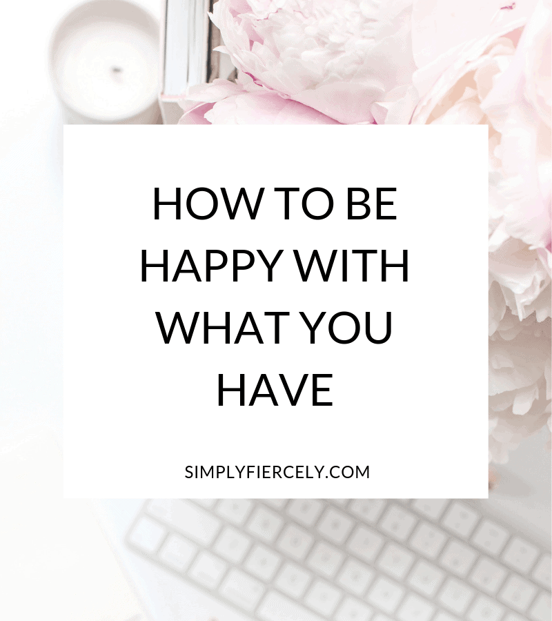 "Title ""How to Be Happy With What You Have"" in a white box with a pink flowers and a white styled flat lay desk in the background."