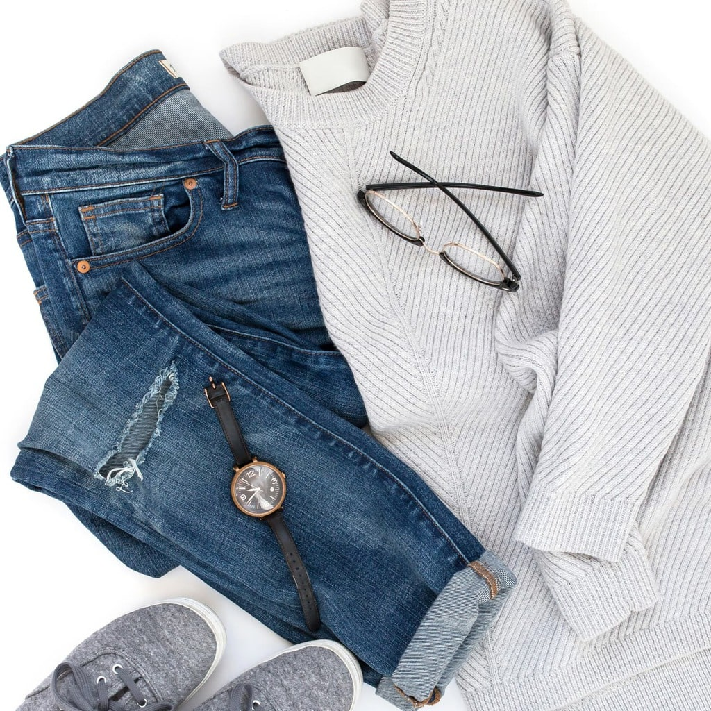 Flat lay with grey sweater, blue jeans, grey shoes, a watch and glasses, against a white background