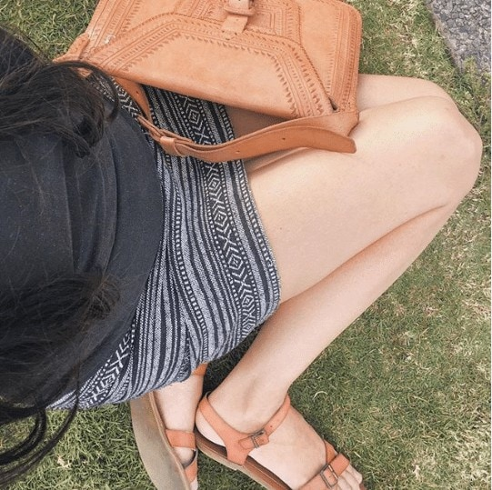 woman with black top and printed skirt kneeling in the grass with a tan leather bag and sandals