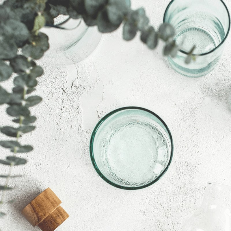 Two glasses on a table top with eucalyptus leaves and a cork bottle stopper.
