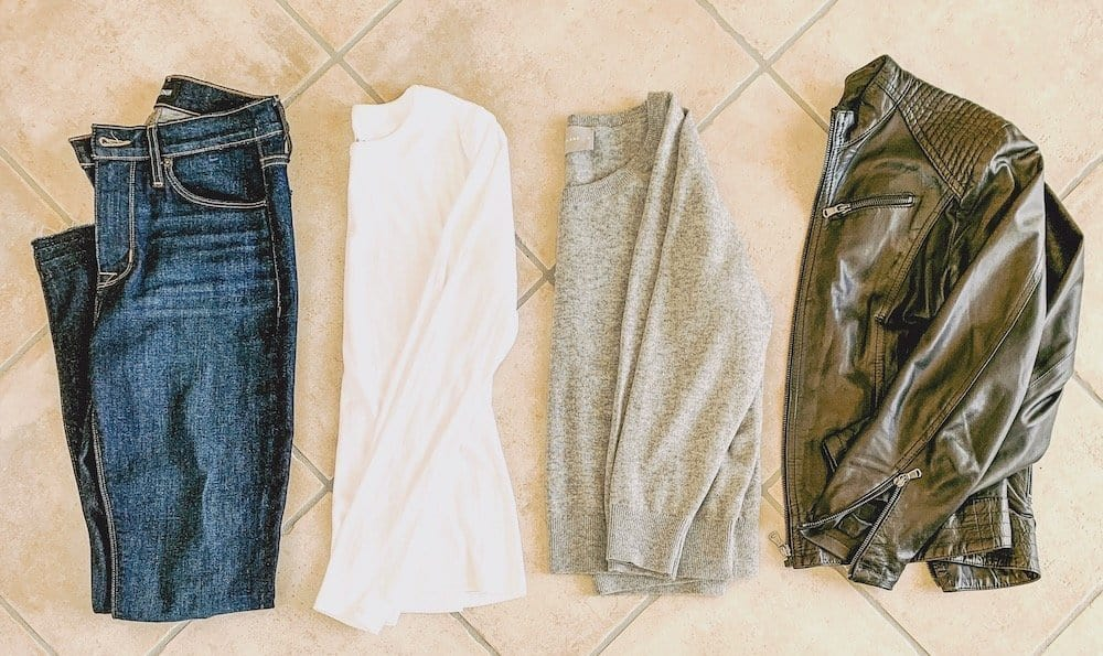 Minimalist winter outfit staples: jeans, a long sleeve shirt, a grey sweater and a leather jacket.
