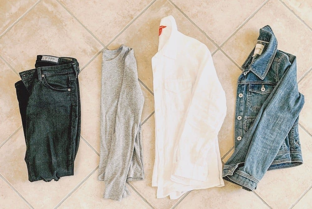 Minimalist winter outfit staples: black jeans, a grey long sleeve shirt, a white button down and a denim jacket.