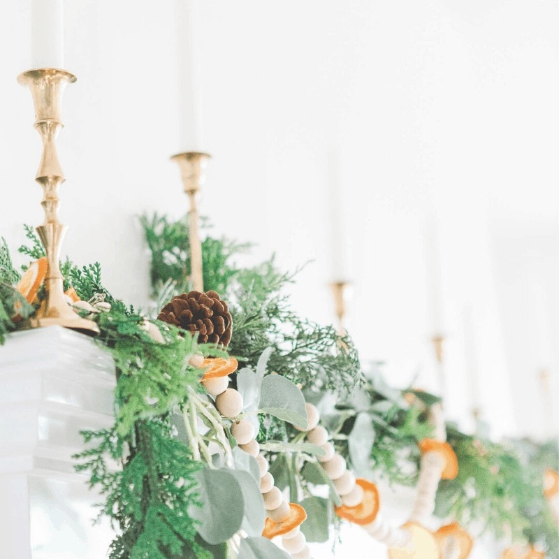 Minimalist Christmas decorations including greenery and garland with dried oranges.