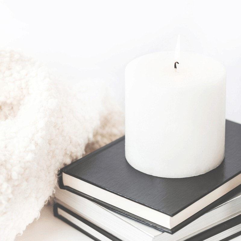 A stack of intentional living books with a candle and blanket.