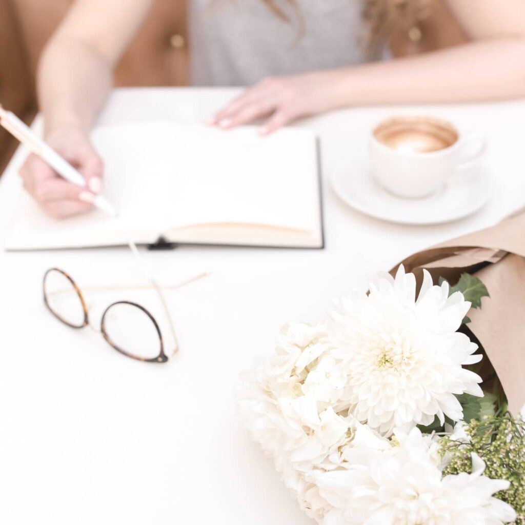 An image of a woman writing in a journal with a cup of coffee, a pair of glasses and a bouquet of white flowers laying on the table beside her.