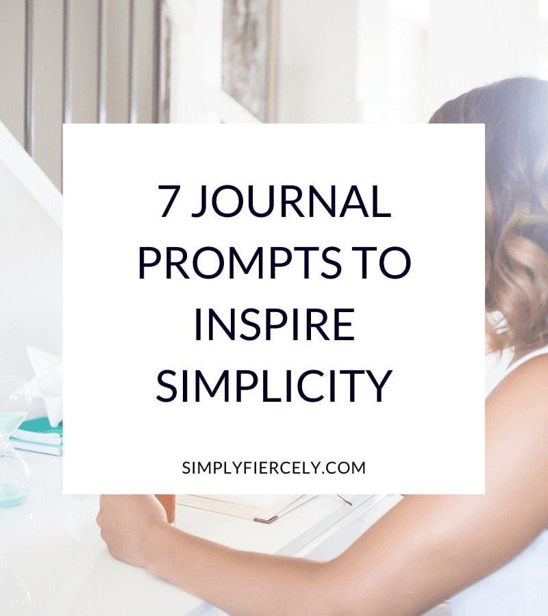 """""""7 Journal Prompts To Inspire Simplicity"""" in a white box with a woman sitting at a desk drinking tea and writing in a journal in the background."""