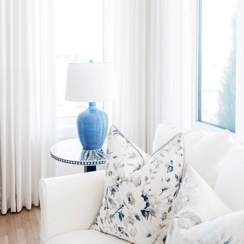 A minimalist room with a white sofa, blue lamp on a side table, and a floral pillow.