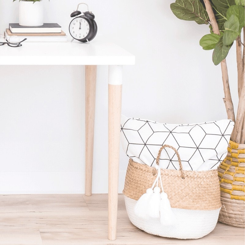 A desk with minimalist accessories, a basket, and a plant.