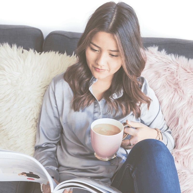 A woman sitting on a sofa drinking tea and reading a book.