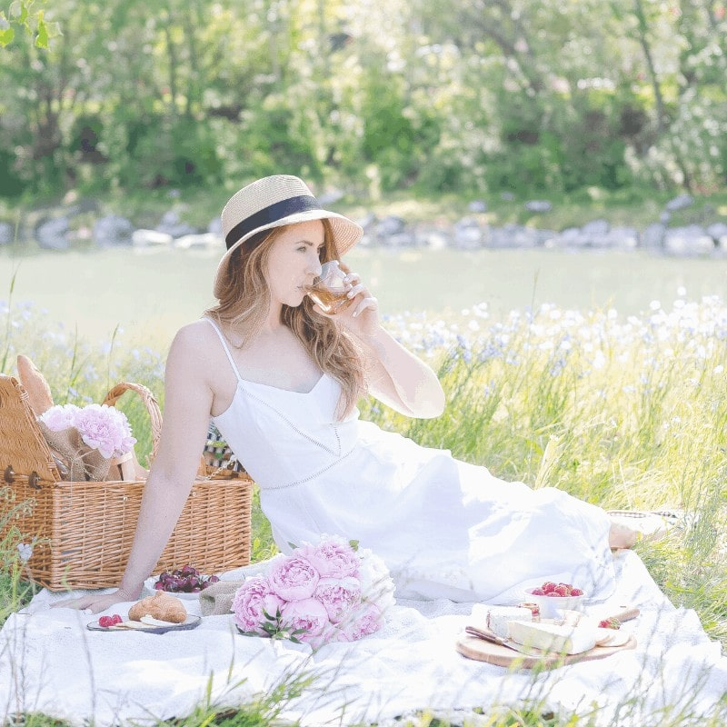 Woman sitting on a blanket drinking lemonade and having a picnic outside beside a stream.