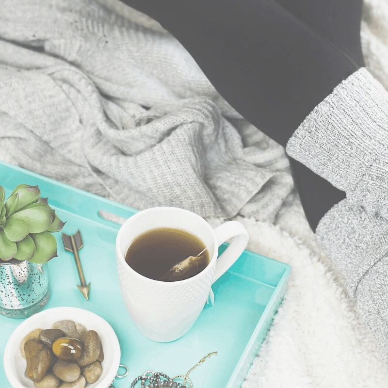 A woman sitting besite a green tray with a cup of tea, a plant, and a bowl of stones on it.