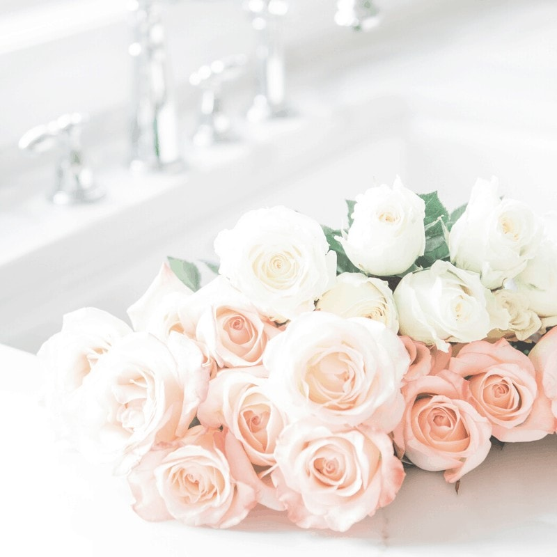 White and peach colored roses laying inside a sink with silver fixtures.