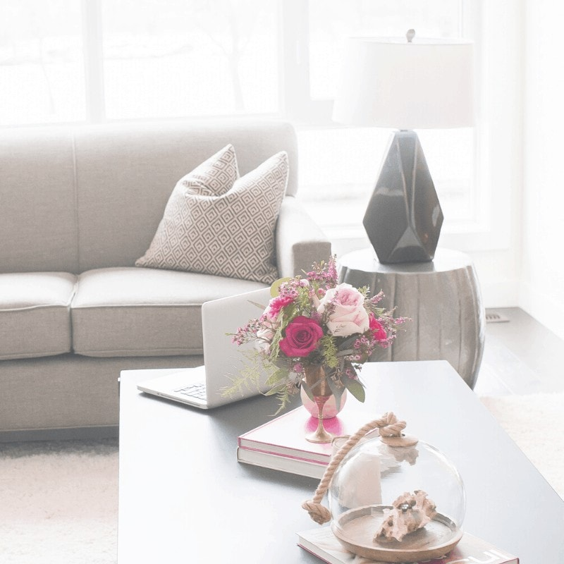A sofa, lamp, and table with books, flowers, and a decorative vase in the background.