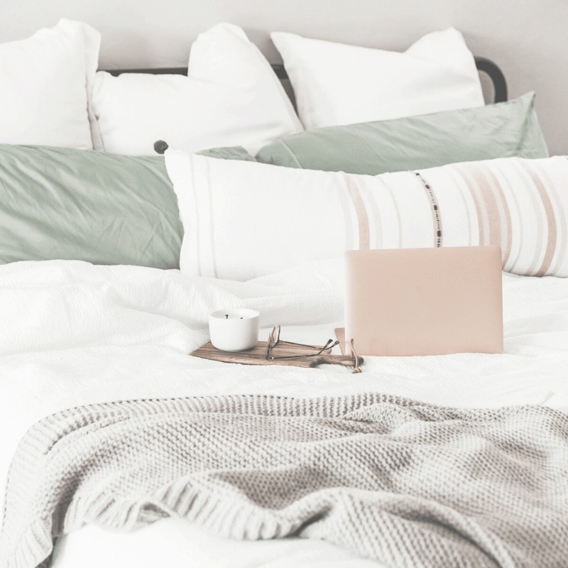 A laptop, cup of tea, glasses, pillows, and a blanket on a bed.