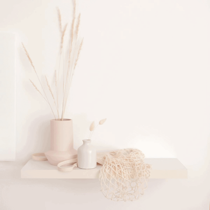 2 vases with decorative wheat and a mesh bag on a shelf.