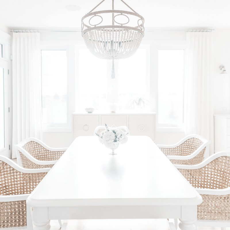 An image of a minimalist dining room with a white dining table, wicker dining chairs, and a chandelier.