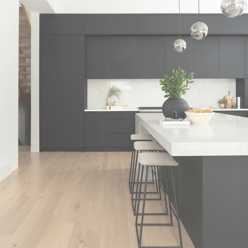 A minimalist kitchen with black cabinets, bar stools, and decorative items on the counter.