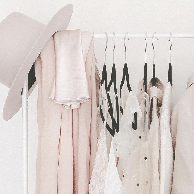 A minimalist wardrobe of  a pink hat and tops hanging on a clothes rack.