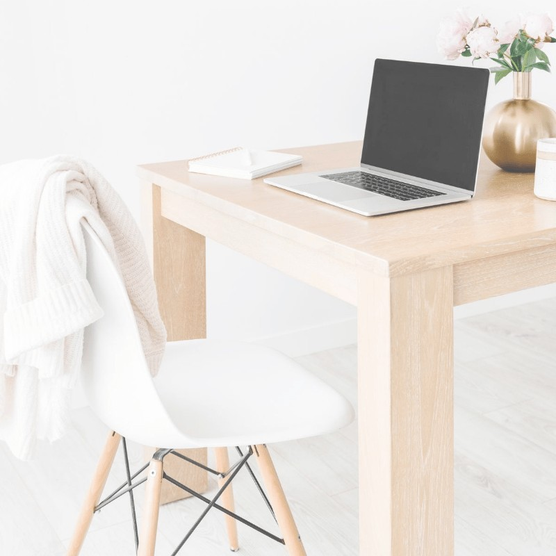 A white chair and a desk with a laptop, notepad, and flowers on it.