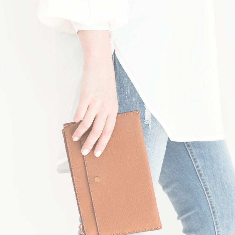 A woman wearing a minimalist outfit of jeans and a white top holding a taupe wallet