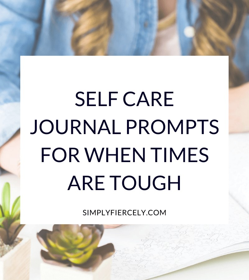 """""""Self Care Journal Prompts For When Times Are Tough"""" in a white box with a woman sitting at a desk writing in a journal in the background."""
