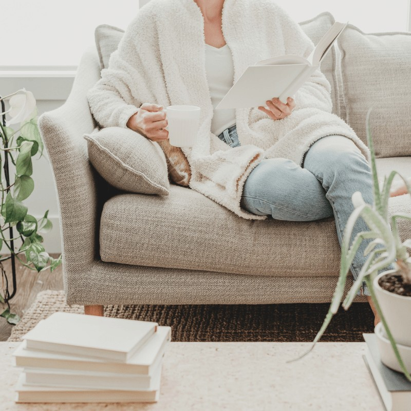 A woman sitting on a sofa reading a book and holding a cup of tea. A table with books and a plant on top in the foreground.