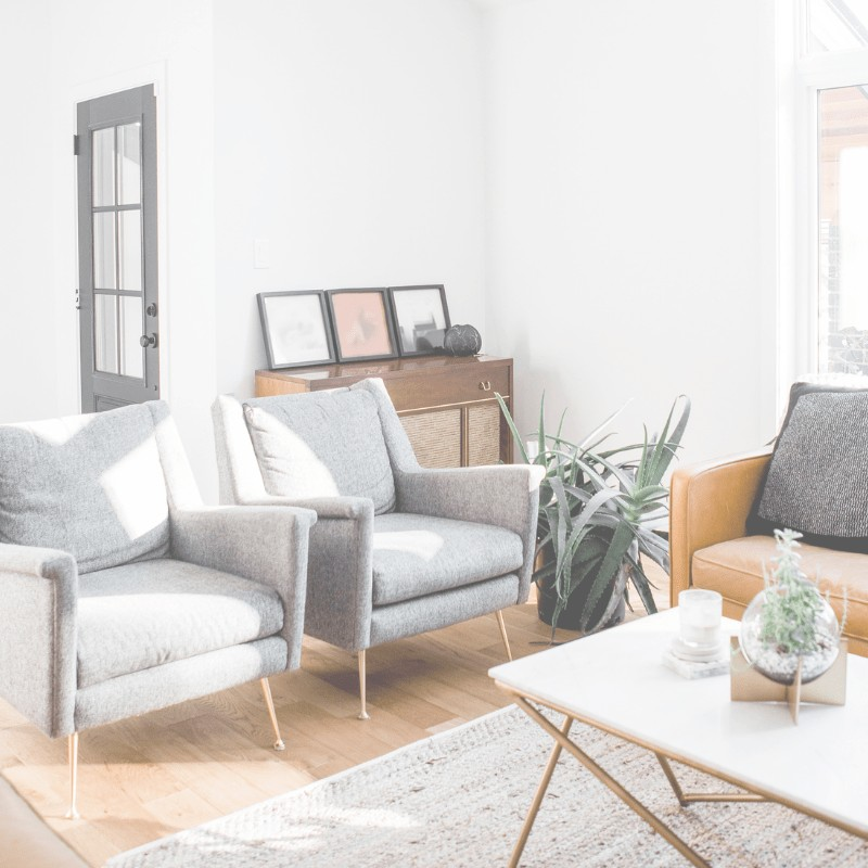 A living room with grey chairs,a plant, pictures, and a table.