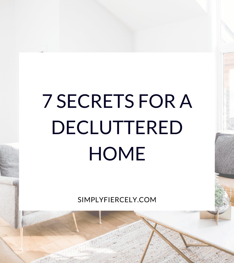 """""""7 Secrets for a Decluttered Home"""" in a white box with a grey sofa and table in the background."""