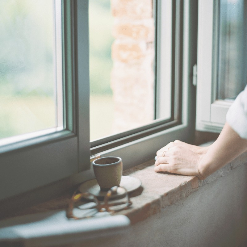 A woman looking out a window with eye glasses and a coffee mug beside her.