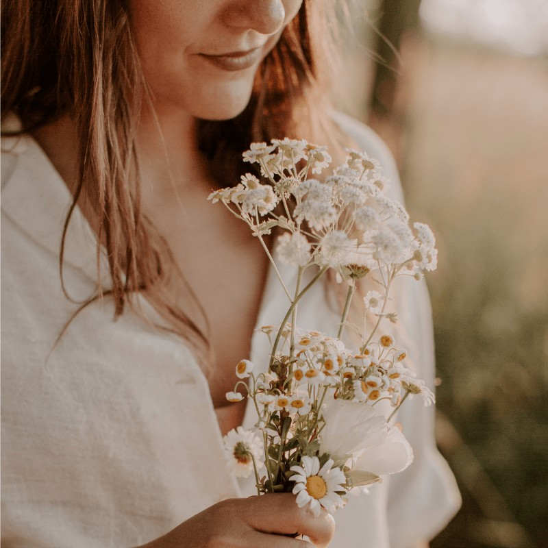 A close up of a woman holding flowers