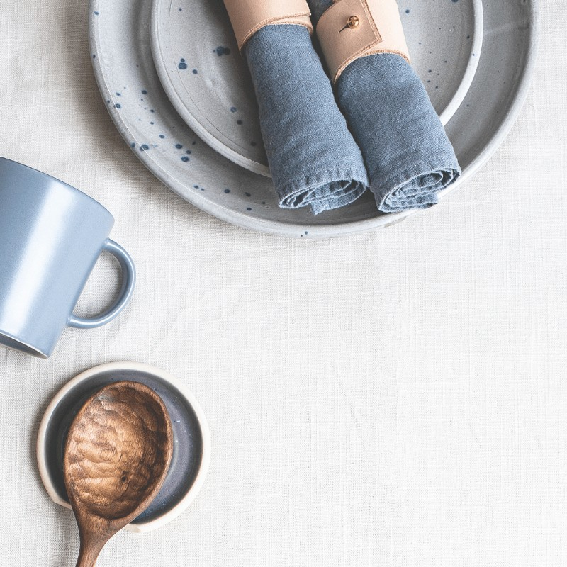 A wooden spoon, blue mug, stack of plates, and 2 blue napkins.