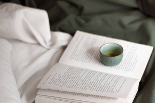 An open book and cup of tea laying on an unmade bed