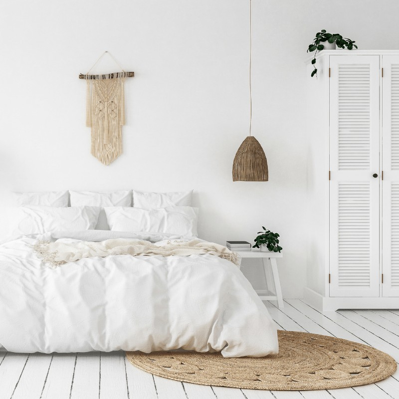 A minimalist bedroom with a white bedspread, tan throw rug, white cabinet and hanging lamp