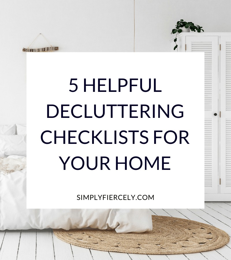 """""""5 Helpful Decluttering Checklists For Your Home"""" in a white box with a minimalist bedroom with a white bedspread, tan throw rug, white cabinet and hanging lamp in the background"""