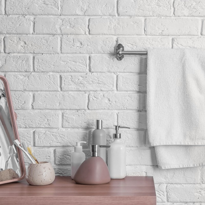 A minimalist bathroom counter with toothbrushes in a cup, soap dispenser, and towel hanging on the wall.