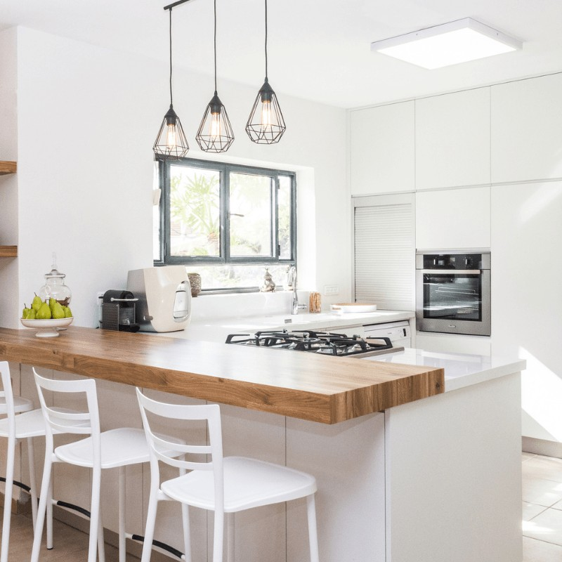 A minimalist kitchen with a butcher block breakfast bar, appliances, white bar chairs, and hanging lamps.
