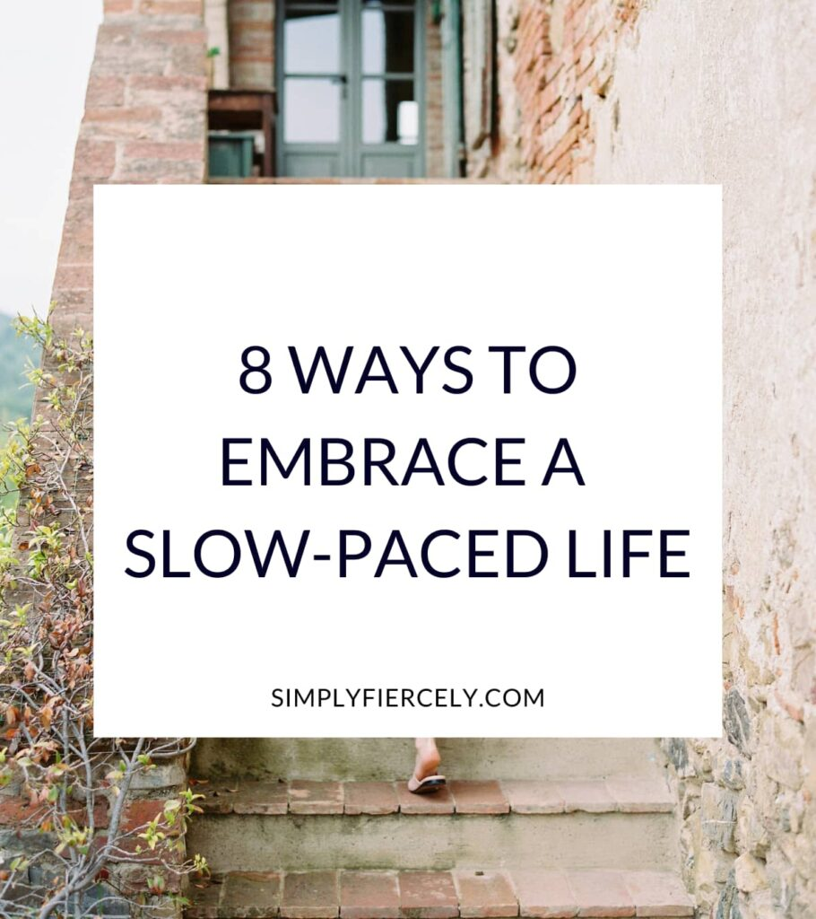 """8 Ways to Embrace A Slow-Paced Life"" in a white box with a woman walking up a rustic outdoor staircase in the background."