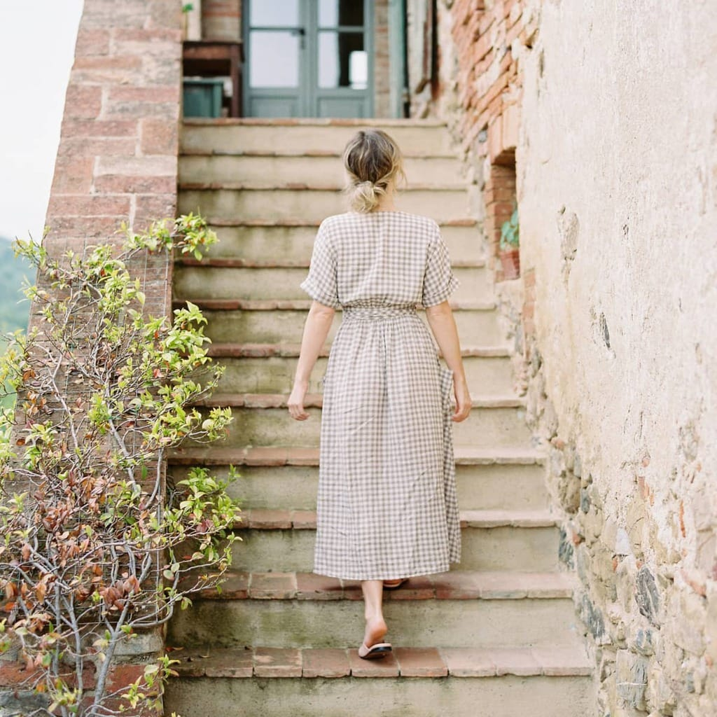 A woman walking up a rustic outdoor staircase.