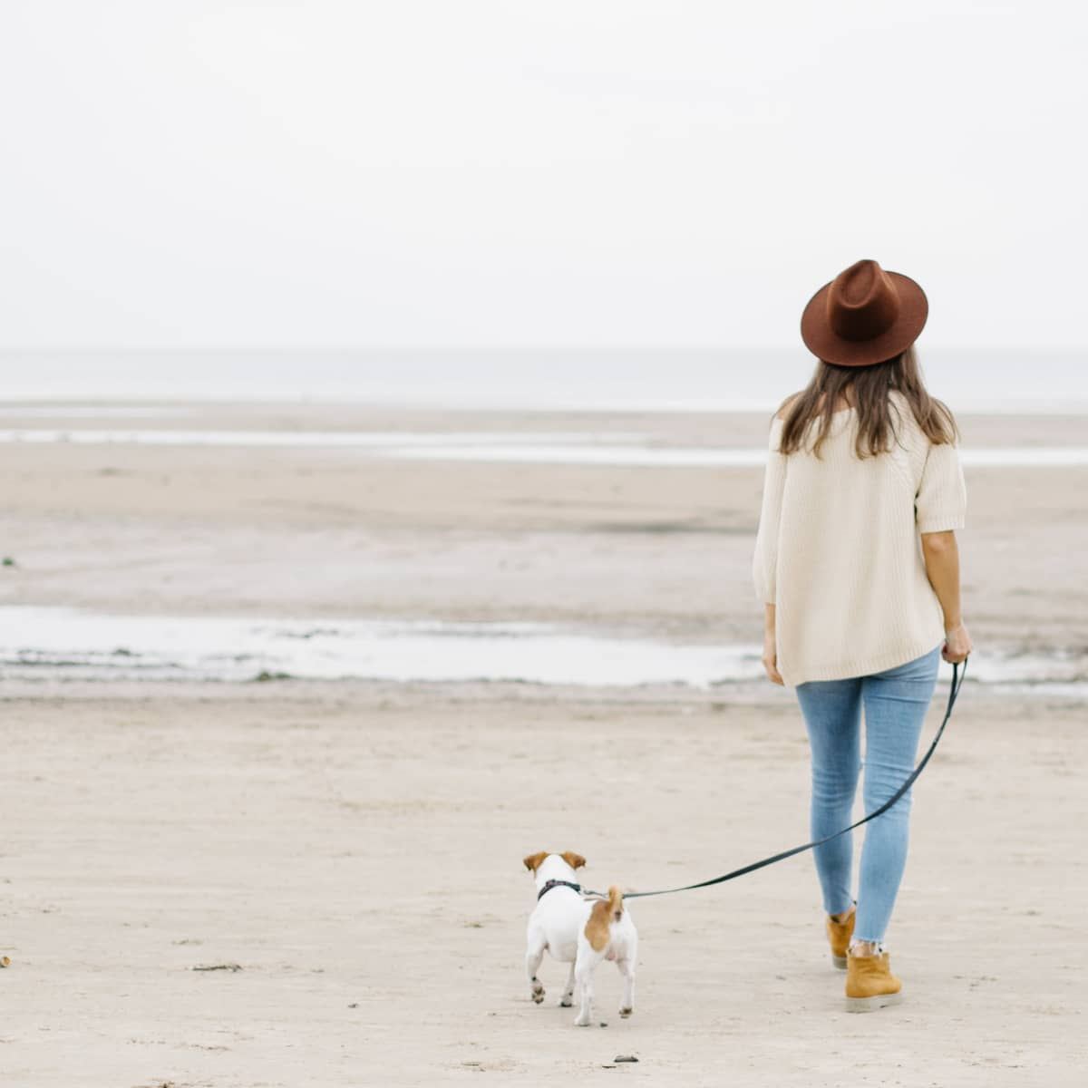 A woman wearing a sweater, jeans, and a hat walking a small dog along the beach.