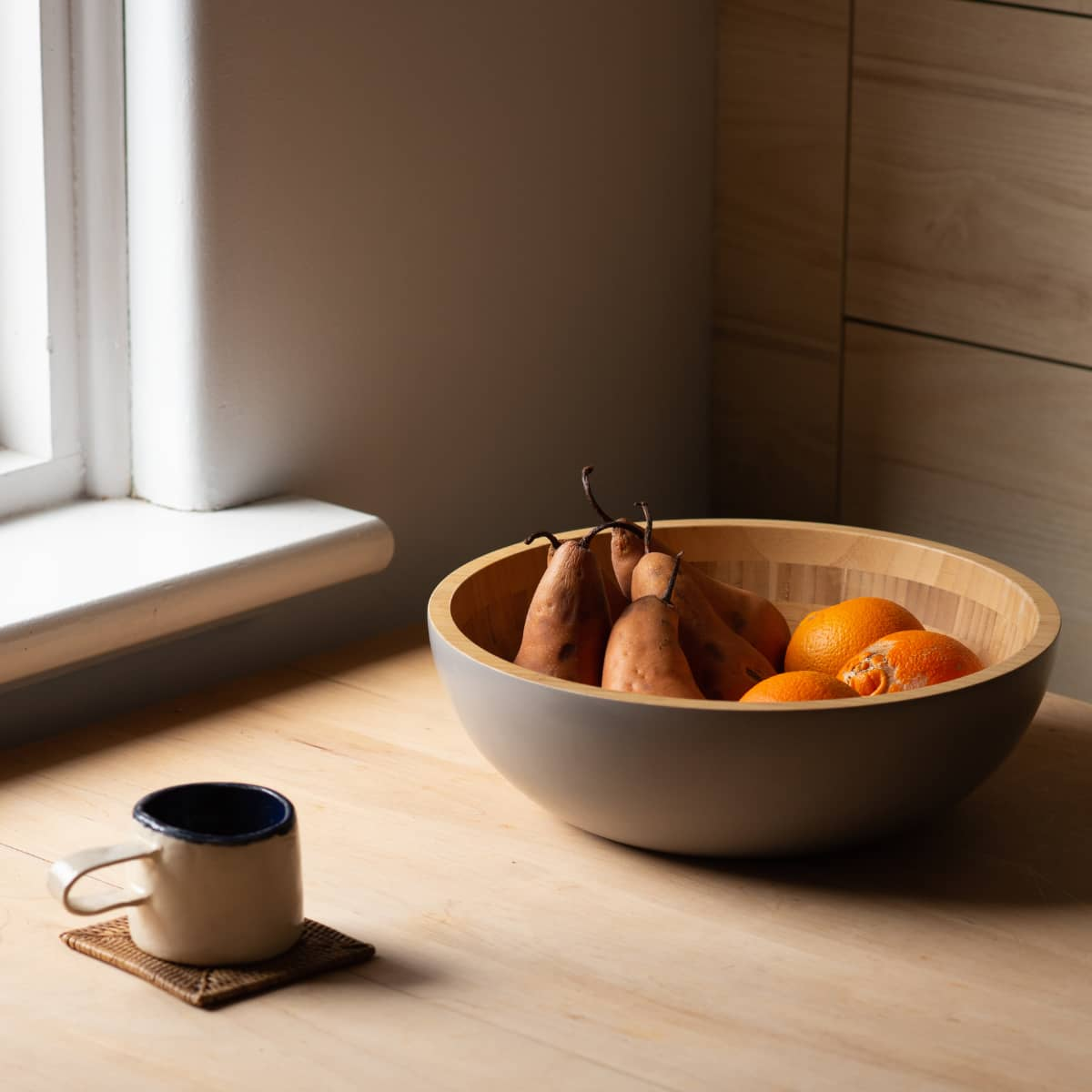 A mug and bowl of fruit sitting on a table in front of a window.