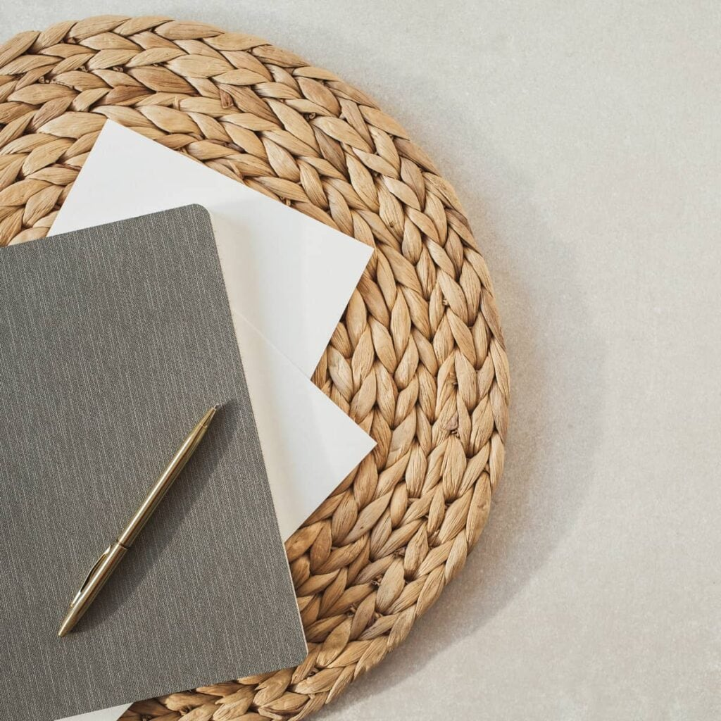A woven mat with sheets of paper, a journal, and gold pen on top.