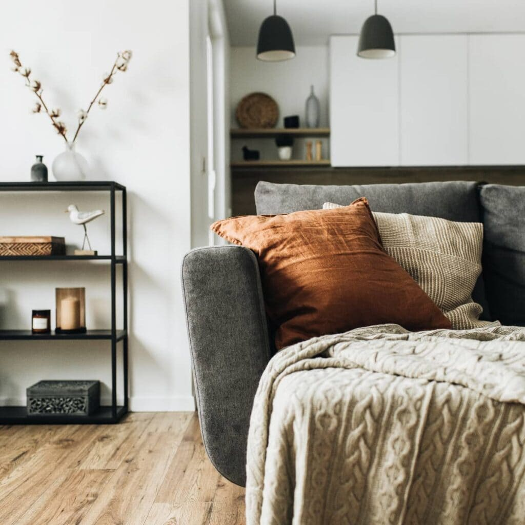 A minimalist home with a sofa and cushions, a bookshelf with knick knacks on it, and hanging lights.